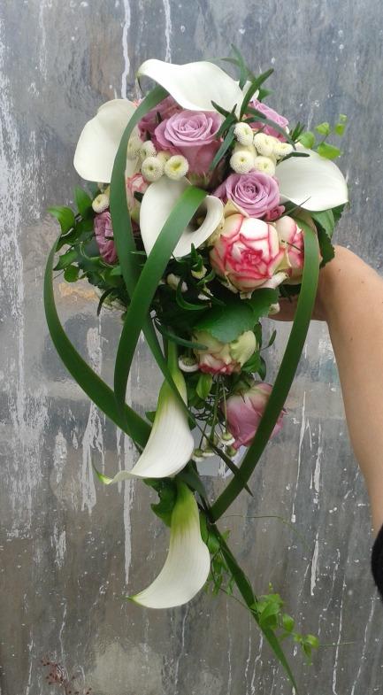 Abfließender Brautstrauß mit Typhablättern, in rosa-violett Schattierungen